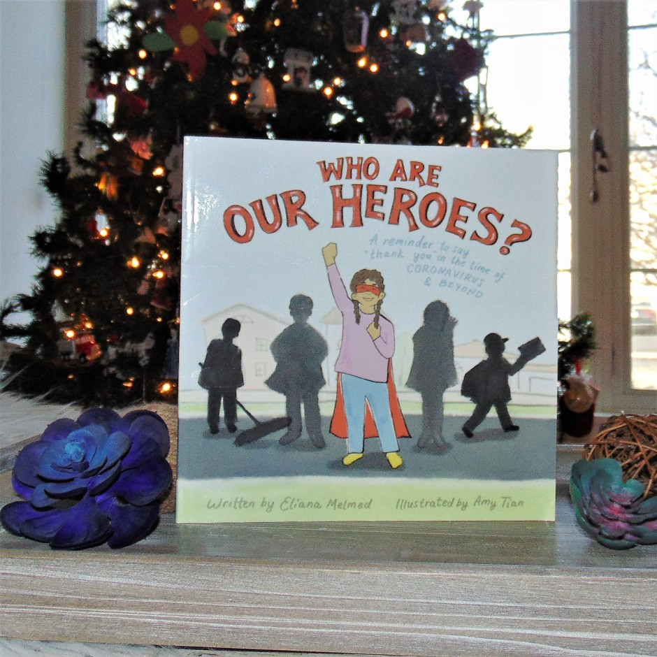 Who are our heroes book in front of christmas tree