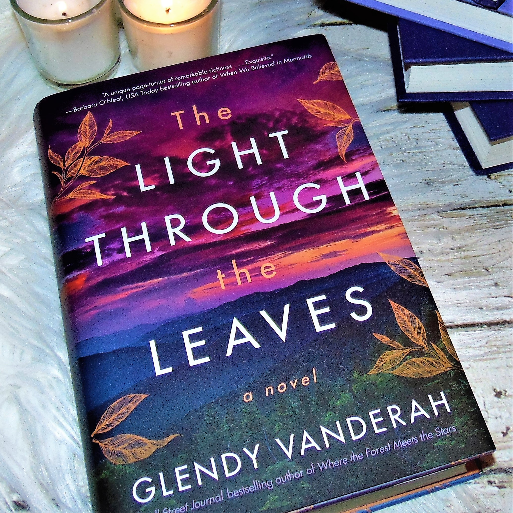 book with sunset on cover and candles