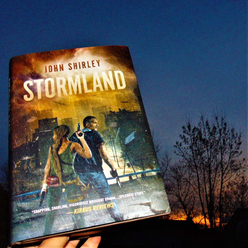 """Book """"Stormland"""" held up to the sky at sunrise"""