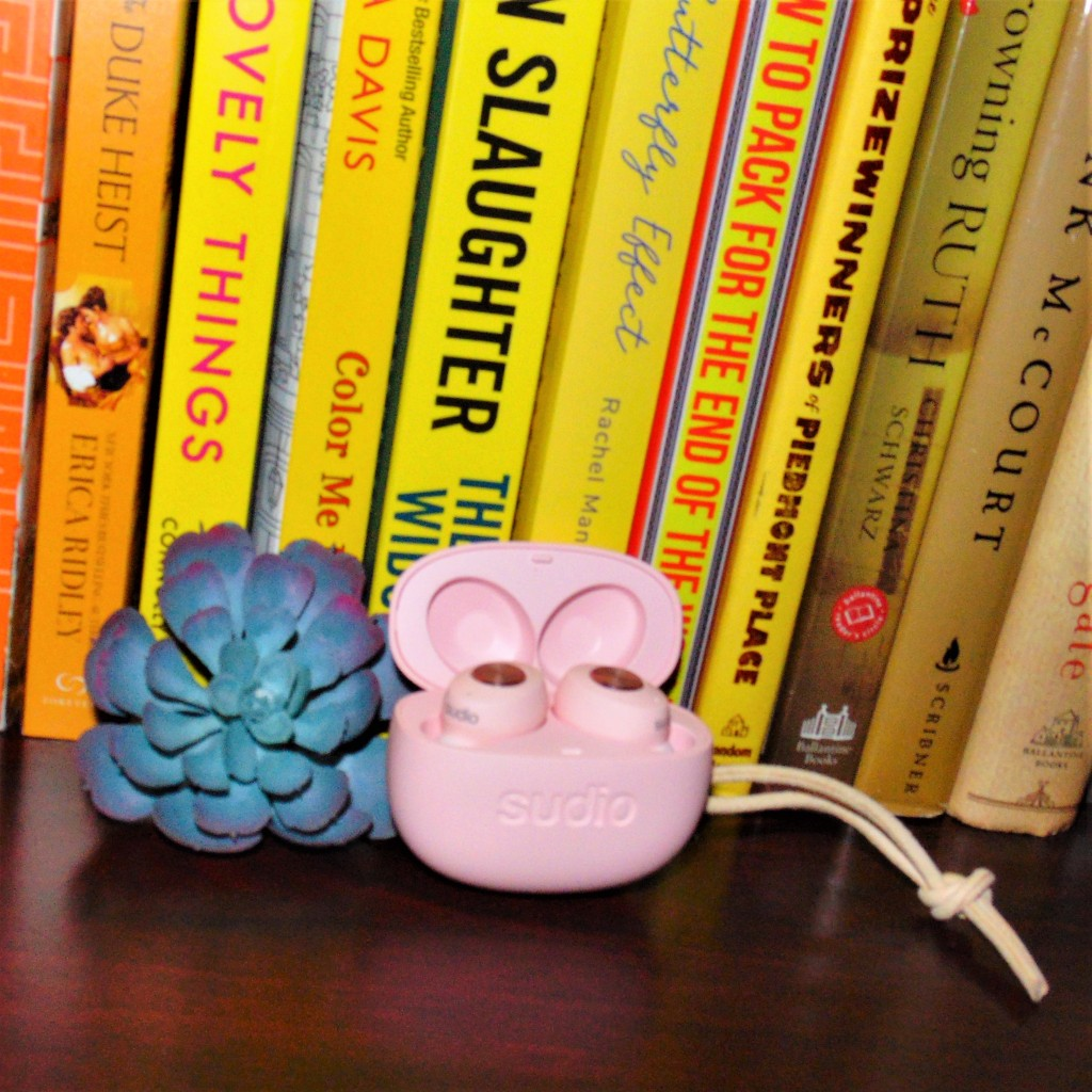 Sudio ear buds in front of books