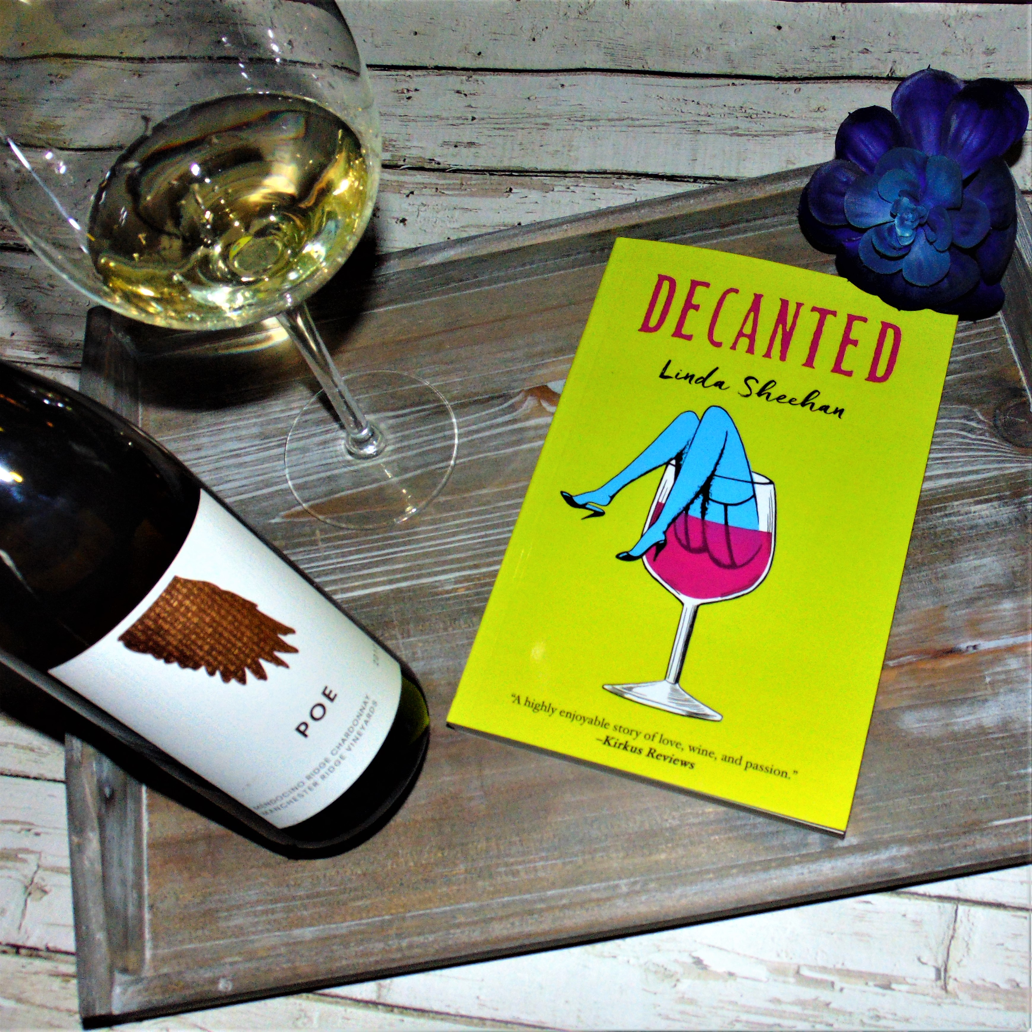 """Book """"Decanted"""" on wooden tray with bottle of win and poured glass of white wine"""