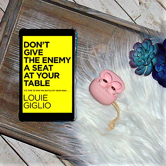 E-Book of Don't Give the Enemy a seat at your table with sudio ear buds on wooden tray