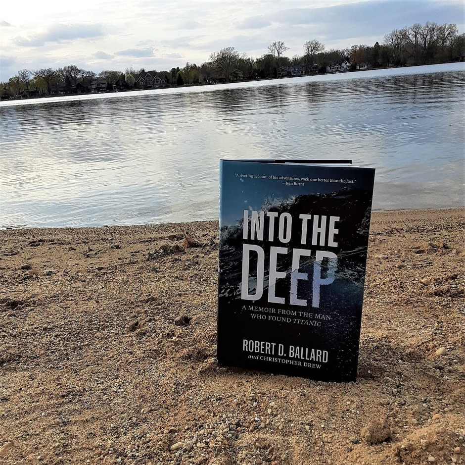"""Book """"Into the Deep"""" in sand at water's edge"""