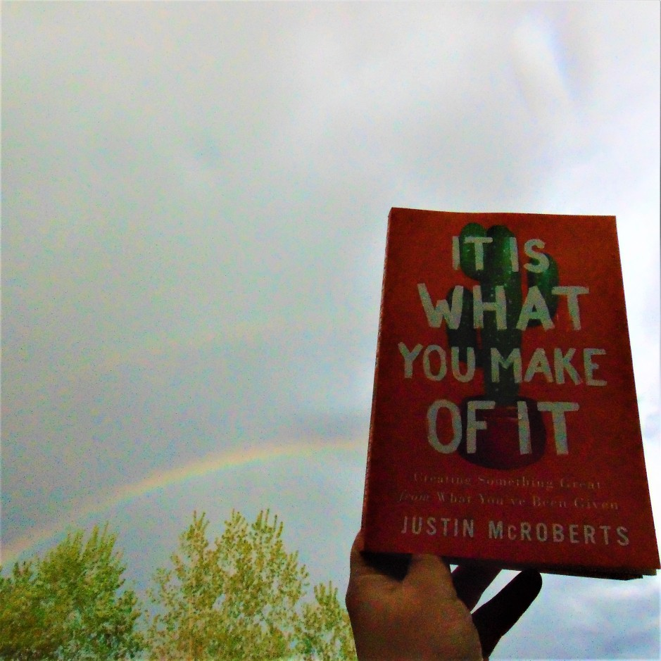 It is what you make of it book held up to sky with rainbow