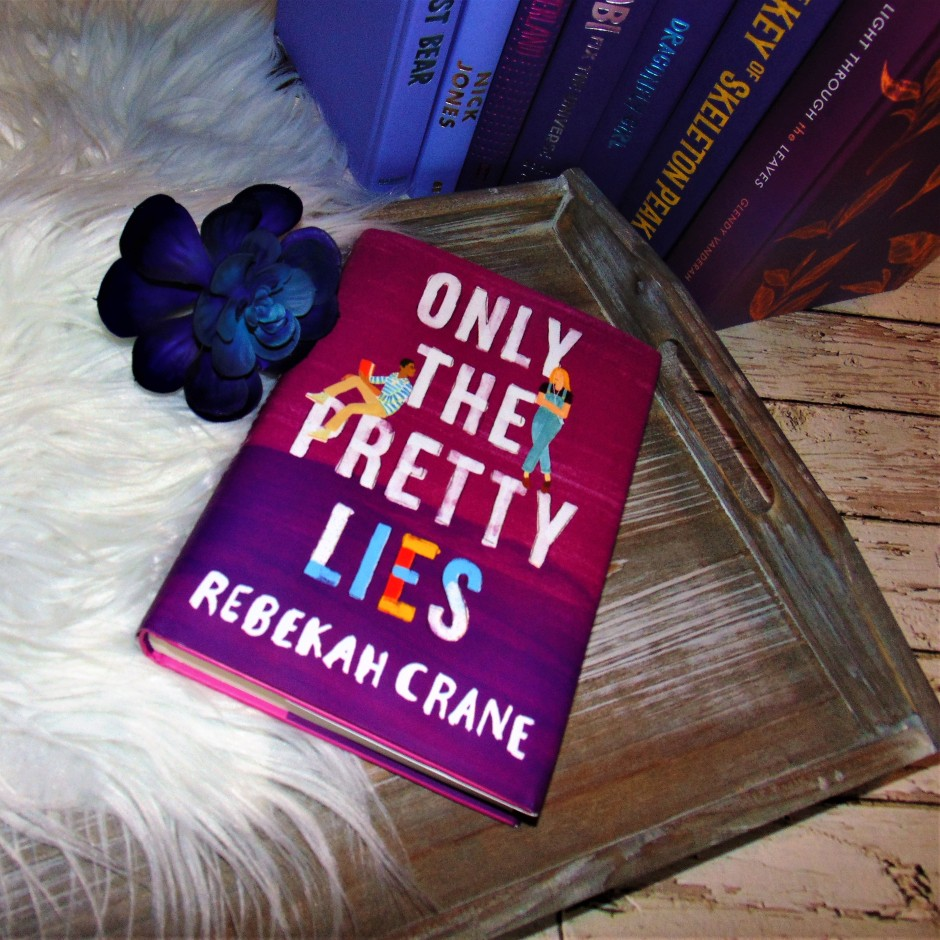 """Book """"Only the Pretty Lies"""" on wooden tray with flower"""