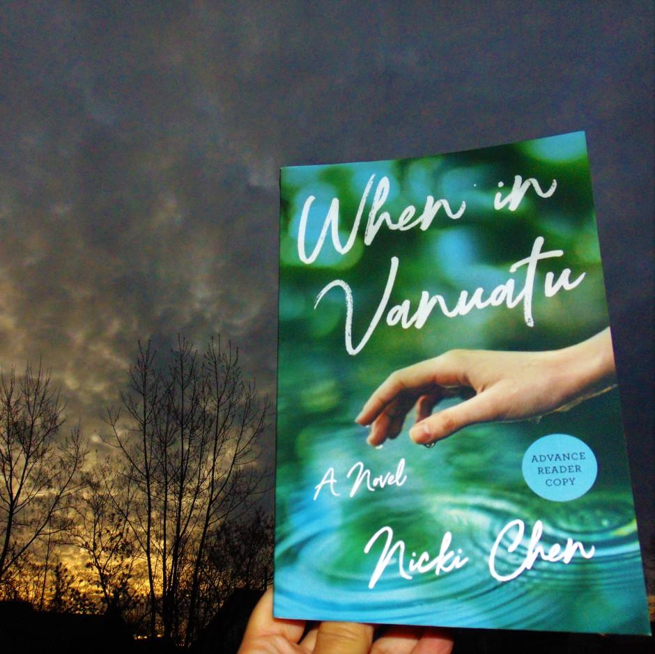 """Book """"When In Vanuatu"""" held up to cloudy sky at sunrise"""