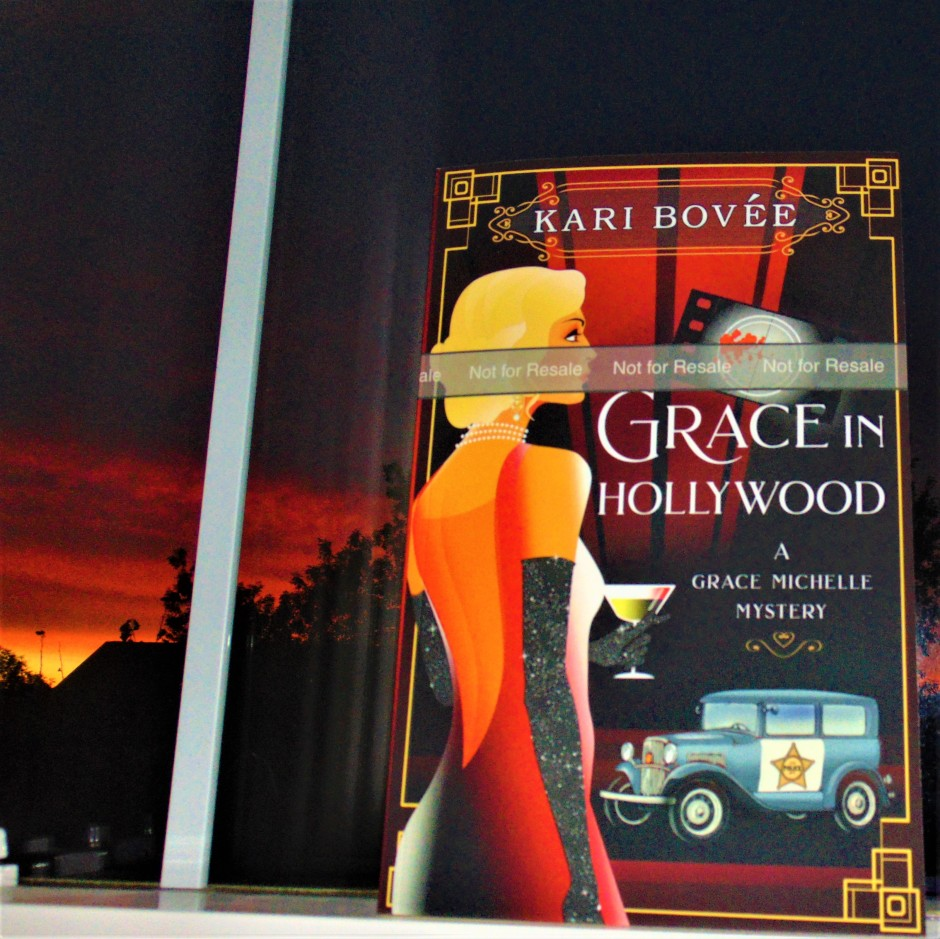 Grace in Hollywood book in window with sunrise in background