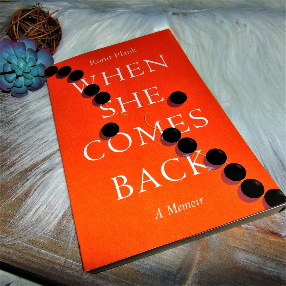 When She Comes Back book on wooden tray with flower