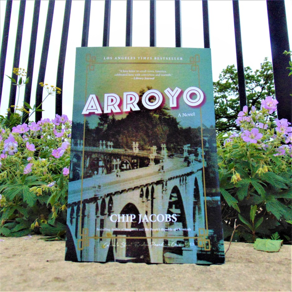 Arroyo book in front of flowers and fence
