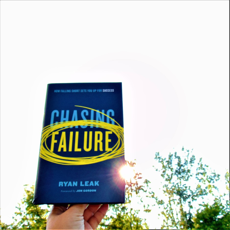 Chasing Failure book held up to sky with sun