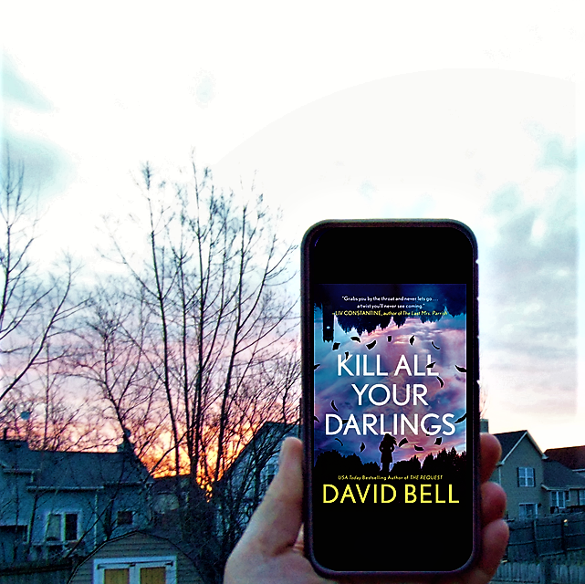 Kill All Your Darlings e-book on phone held up to sunrise