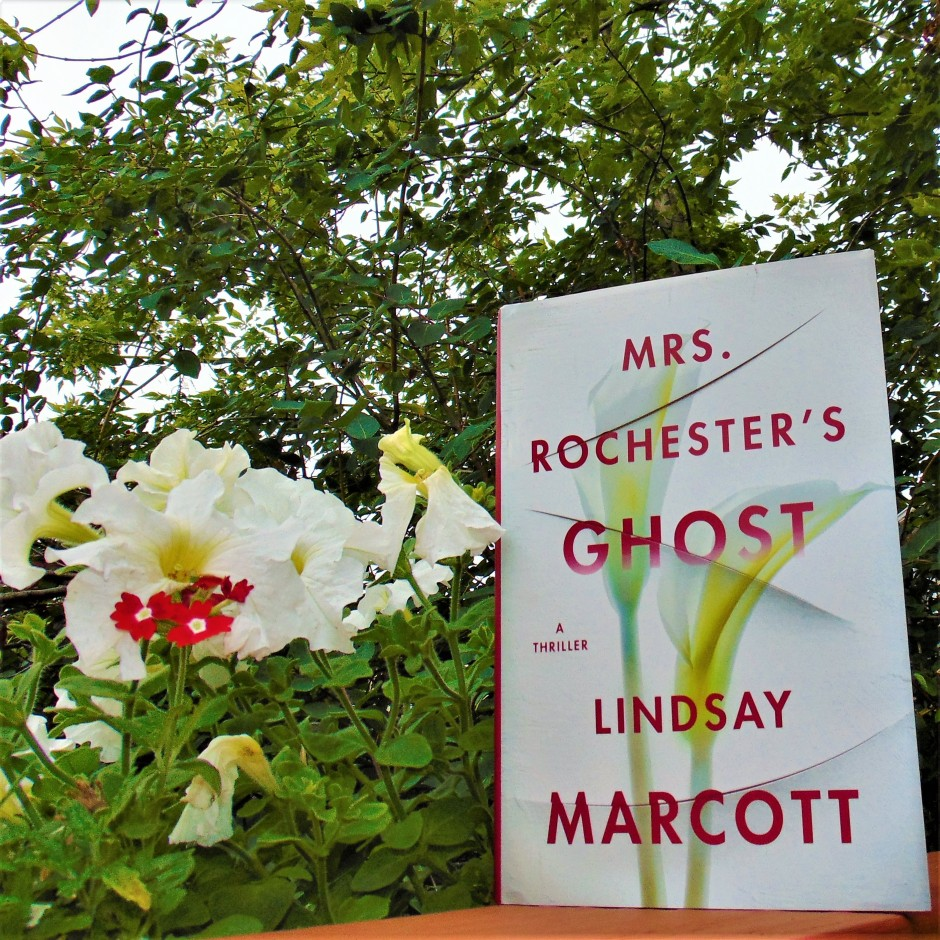 Mrs. Rochester's Ghost book next to red and white flowers