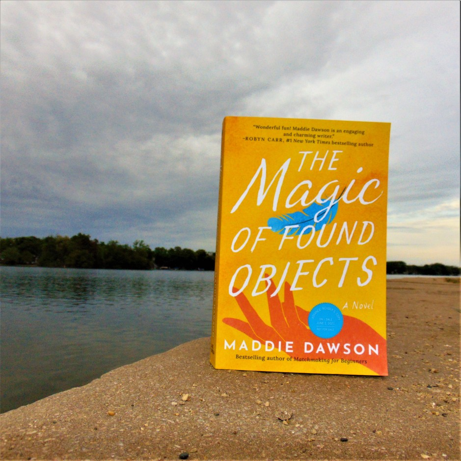 The Magic of Found Objects book sitting on lake edge with cloudy sky