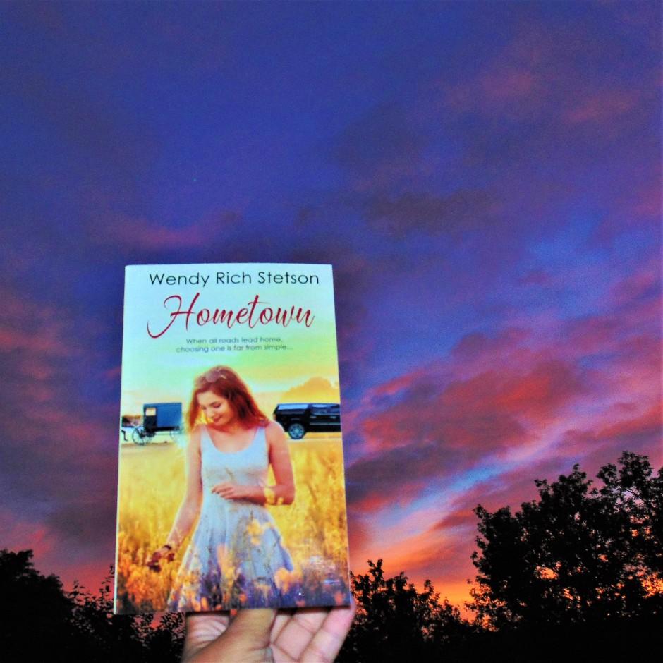 Hometown book held up to sunrise sky