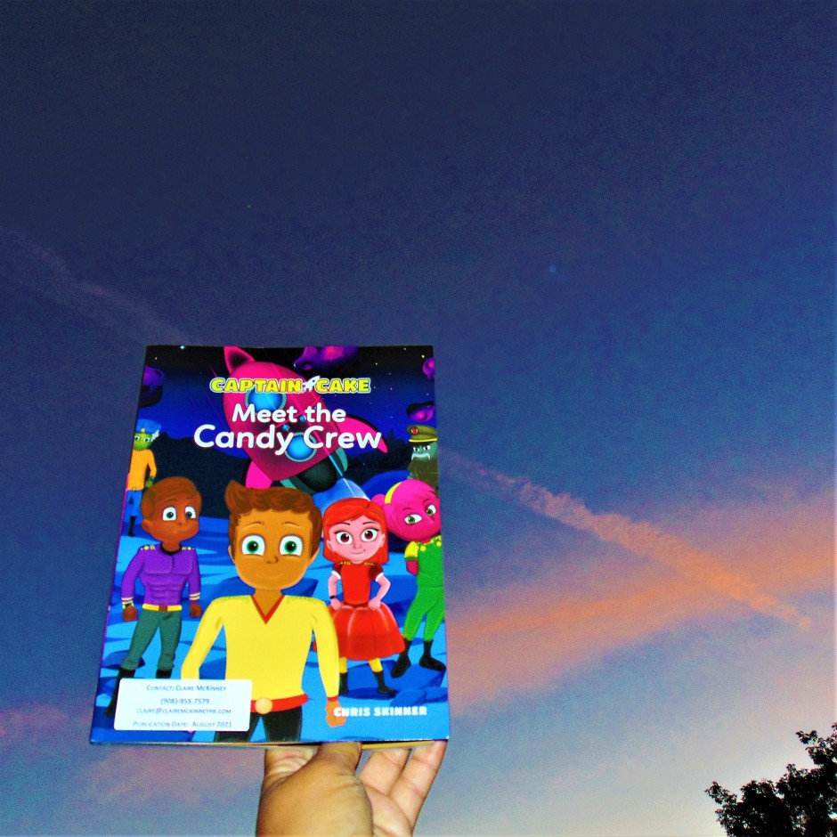 Meet the Candy Crew book held to sky with clouds