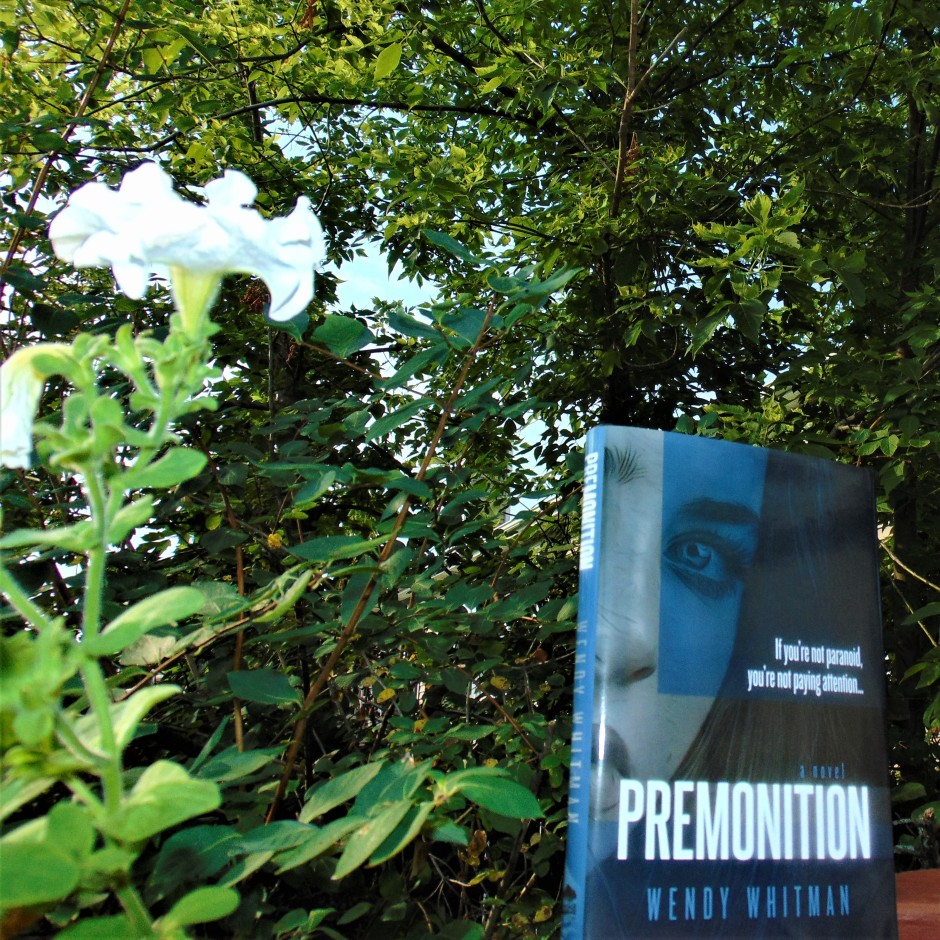 Premonition book in front of trees and flower