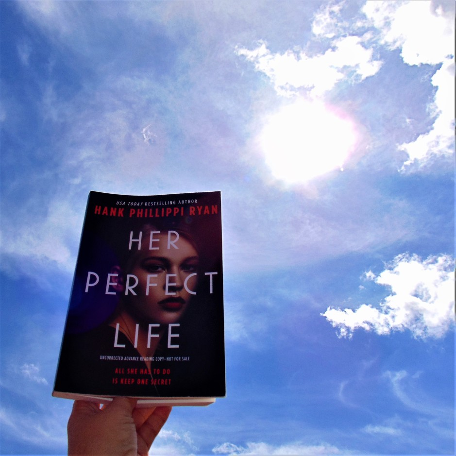 Her Perfect Life book held to sunny sky