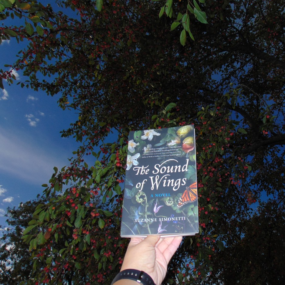 The Sound of Wings book held up to tree and sky