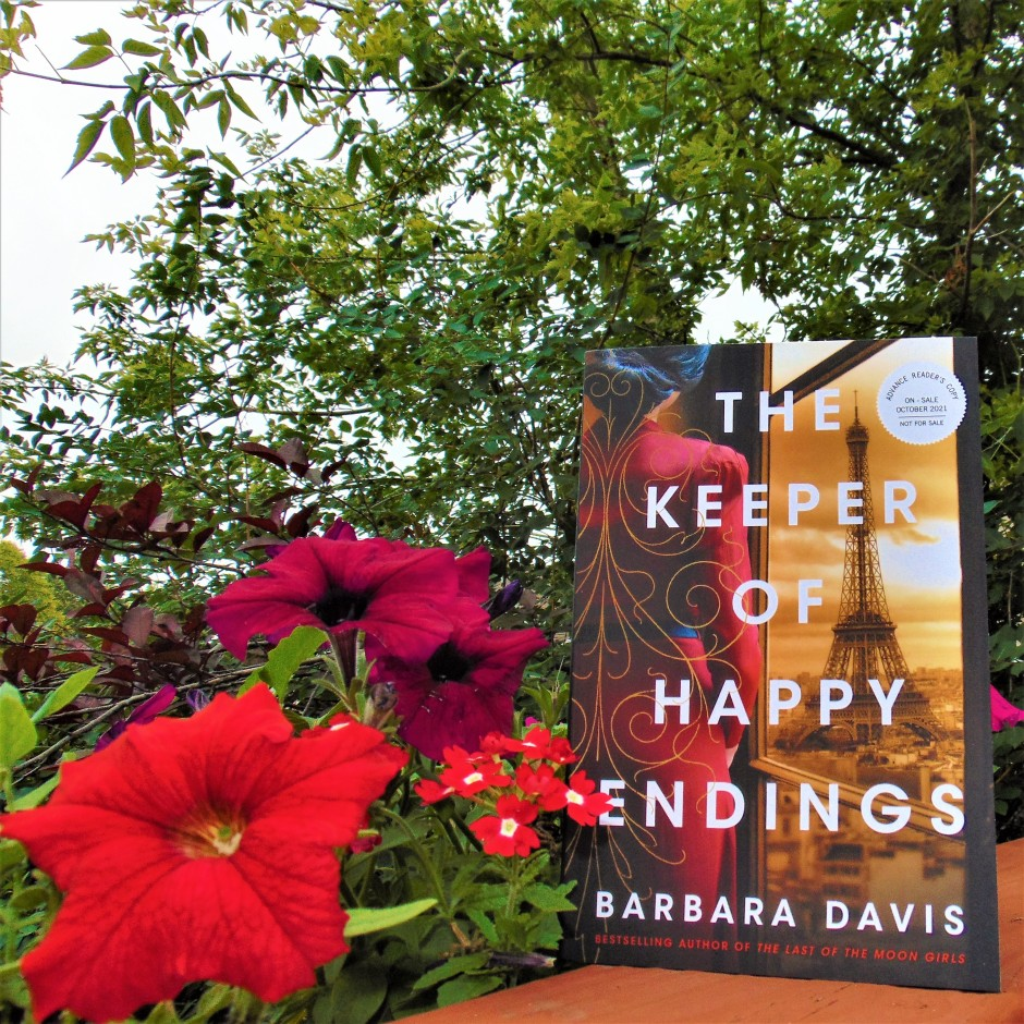 The Keeper of Happy Endings book next to flowers