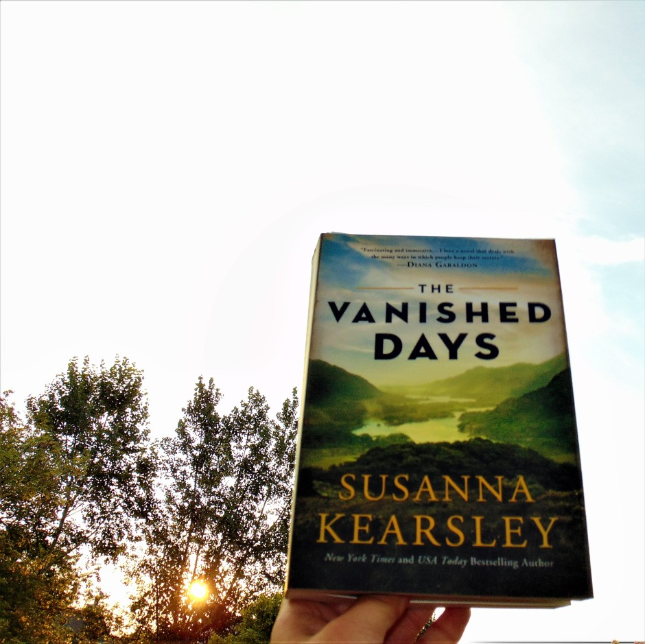 The Vanished Days book held to sky with sun shining through trees